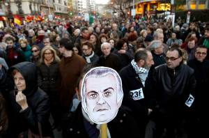 A man holds a picture of former People's Party (PP) treasurer Luis Barcenas investigated for bribery during a demonstration against austerity measures and political corruption in Valencia